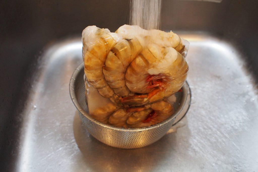 冷凍エビを解凍中。わりと適当に流水をあててしまって大丈夫です。